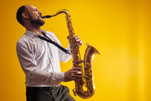 Portrait Of Professional Musician Saxophonist Man In  White Shirt Plays Jazz Music On Saxophone, Yellow Background In A Photo Studio, Side View