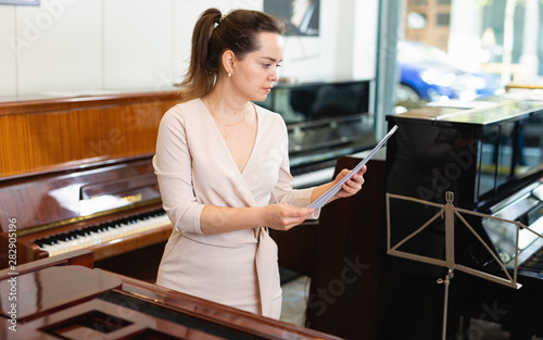 Fotobehang Muziekwinkel Pretty woman seller in piano music store