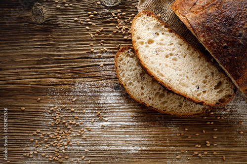 Obraz na plátne Bread,  traditional sourdough bread cut into slices on a rustic wooden background, close-up, top view, copy space