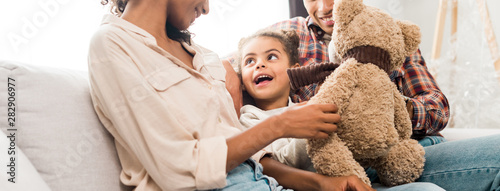Fotografie, Obraz  panoramic shot of african american family sitting on sofa while kid holding tedd