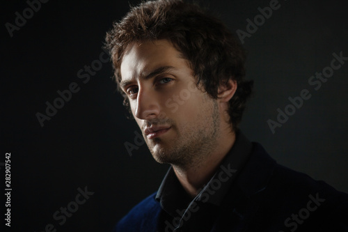 Fotografía Handsome young brunette man with light eyes in dark clothes looks into the distance