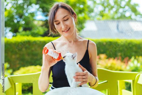 Cuadros en Lienzo Young smiling woman feeding with milk a white cute kitten from a bottle - growin