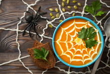 A Healthy Pumpkin Puree Garnished With Cream And Parsley Leaves. Composition Autumn Cream Soup With Toys For The Holiday Halloween On A Dark Wooden Background, Top View.
