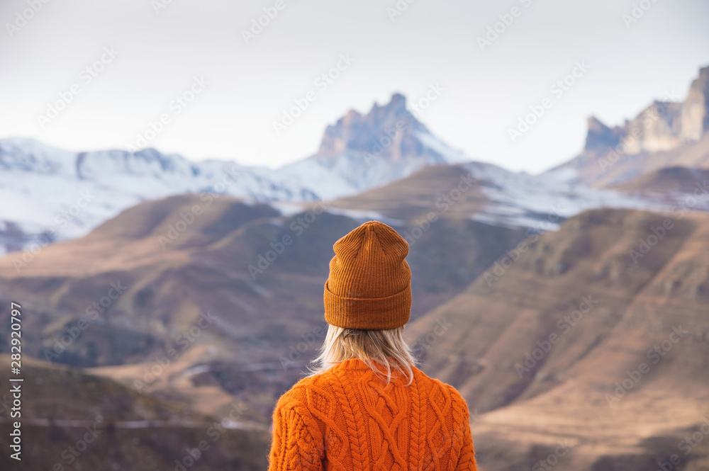 Fototapety, obrazy: Portrait from the back of the girl traveler in an orange sweater and hat in the mountains against the background of a frozen mountain. Photo travel concept