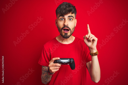 Fotografía Young gamer man with tattoo playing video game standing over isolated red backgr