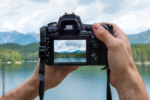 Obraz Hands of a male photographer holding a digital camera taking pictures of a idyllic landscape with a lake and mountains while the picture shows at the display - fototapety do salonu