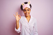 Young african american woman wearing pajama and mask over isolated pink background smiling positive doing ok sign with hand and fingers. Successful expression.