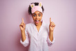 Young african american woman wearing pajama and mask over isolated pink background smiling amazed and surprised and pointing up with fingers and raised arms.
