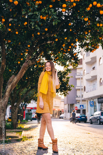 girl on city street in dress and scarf  trees with oranges