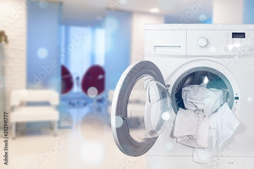 Washing machine with laundry on background