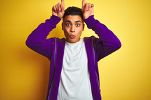 Young Brazilian Man Wearing Purple Sweatshirt Standing Over Isolated Yellow Background Doing Funny Gesture With Finger Over Head As Bull Horns