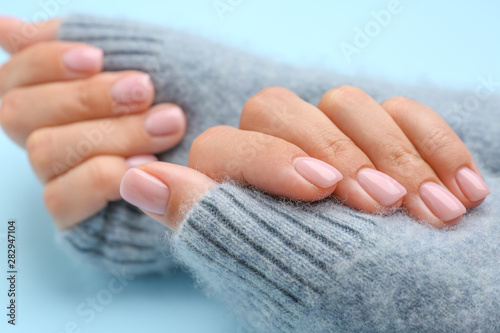 Vászonkép Hands of woman with beautiful manicure on color background, closeup