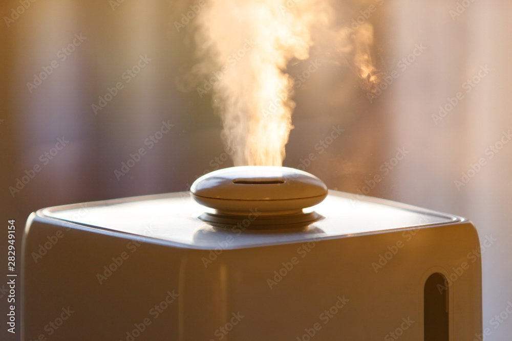 Fototapety, obrazy: Close up of aroma oil diffuser on the table at home, steam from the air humidifier. Ultrasonic technology, increase in air humidity indoors, comfortable living conditions.