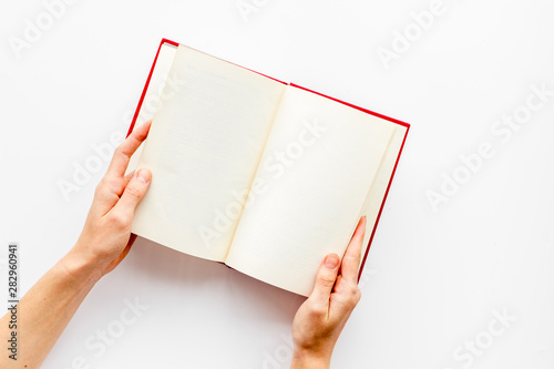 Book in hands for reading on white library desk background top view space for te Tablou Canvas