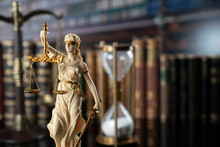 The Law Concept Background.  White Statue Of Themis And Legal Books On The Table In The Old Court Library.