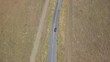 4K drone shot moving forward down country road tilt up slowly to reveal beautiful landscape and long road winding through California rural fields, stretching out as far as eye can see
