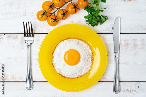 Fototapeta fried egg on yellow plate with cherry tomatoes. Fork and knife. Light breakfast. obraz
