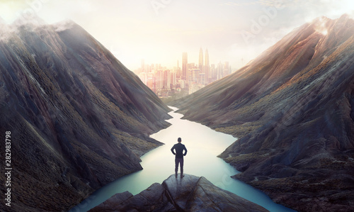 Tuinposter Wit Businessman on top of the hill watching wonderful scenery in mountains with lake during dramatic sunset .Business ambition and success concept.