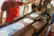El Hombre Está Haciendo Tortillas De Maíz En Una Maquina Antigua.