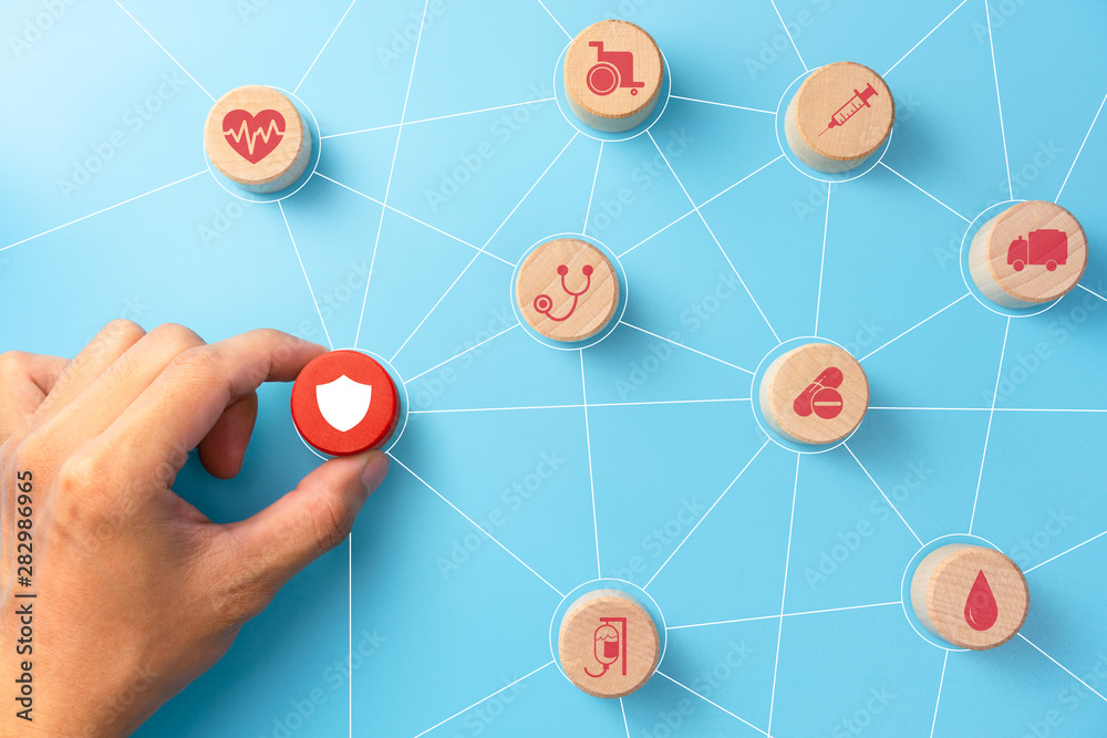 Fototapety, obrazy: Health insurance concept, Hand holding a wooden cubes with healthcare medical icon, blue background