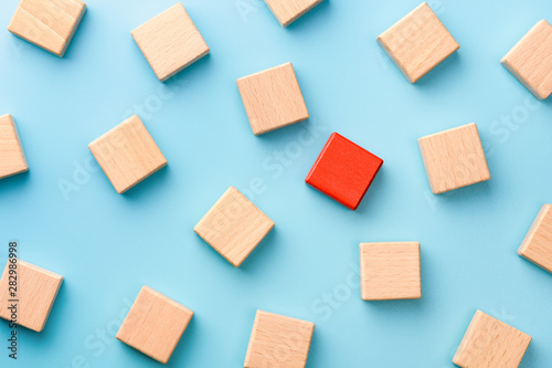 Photo Red wooden block standing out from the group wooden blocks on blue background