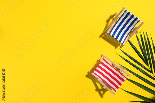 Billede på lærred Deck chair with hard shadow, palm leaves on yellow paper background