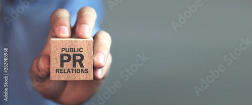 Fotografie, Tablou Man holding wooden cube. Pr- Public Relations
