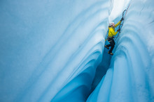 Ice Climbing Between Canyon Walls Covered In Wavy Lines Carved By Meltwater.