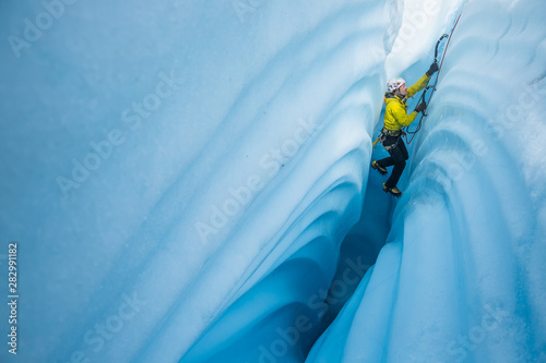 Ice climbing between canyon walls covered in wavy lines carved by meltwater Canvas Print