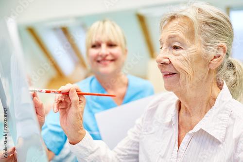 Leinwand Poster Senior Frau im Malkurs in einer Maltherapie
