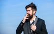 Recovery from nicotine addiction must involve changing our relationship to smoking. Man beard and mustache hold cigarette. Bearded hipster smoking cigarette blue sky background. Guy enjoy cigarette