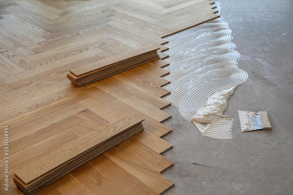 Fototapeta Worker laying parquet flooring. Worker installing wooden laminate flooring - obraz na płótnie