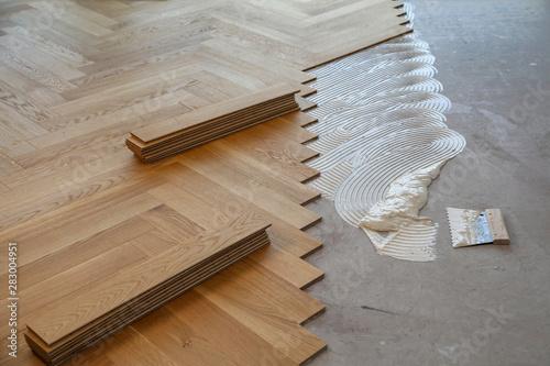 Fototapeta Worker laying parquet flooring. Worker installing wooden laminate flooring obraz na płótnie