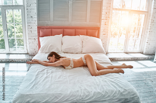 Fotografie, Obraz  The cute woman in underwear laying on the bed
