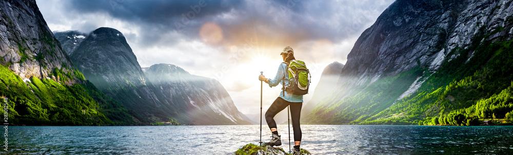 Fototapeta Frau mit Rucksack beim Wandern an einem Fjord in Norwegen