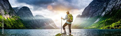 Obraz Frau mit Rucksack beim Wandern an einem Fjord in Norwegen - fototapety do salonu