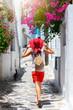Frau mit rotem Sonnenhut geht durch eine kleine Gasse mit bunten Blumen auf den Kykladen in Griechenland