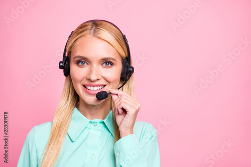 Close up photo of pretty worker having ear phones chatting wearing mint color shirt isolated over pink background