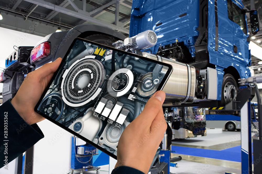 Fototapeta Serviceman repairing a truck using augmented reality application.