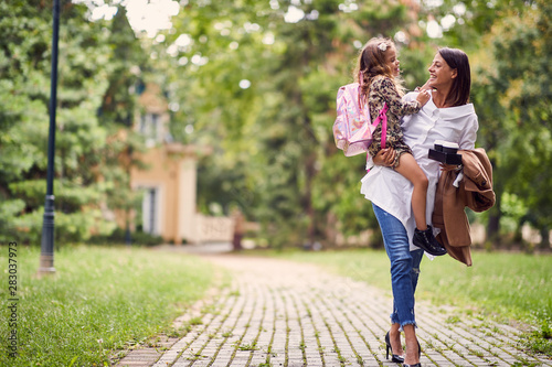 Fototapeta smiling mother holding a daughter with schoolbag obraz