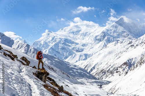 Pinturas sobre lienzo  Strong girl with backpack Osprey stands on the edge of the mountain overlooking the snow-capped peaks of the Himalayas on Annapurna Circuit Trek in Nepal