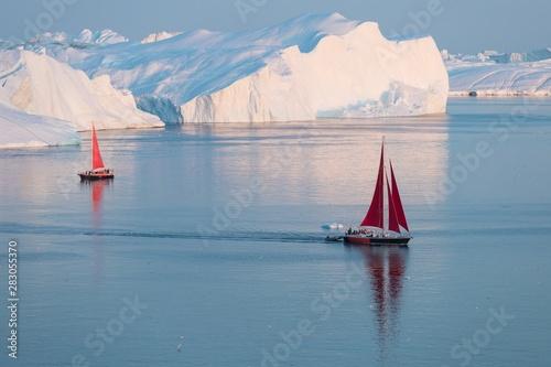 Little red sailboat cruising among floating icebergs in Disko Bay glacier during midnight sun season of polar summer Obraz na płótnie