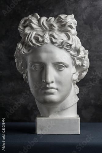 Fototapety, obrazy: Gypsum copy of ancient statue Apollo head on dark textured background. Plaster sculpture man face.