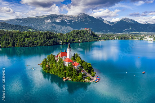 Foto auf Leinwand Blau türkis Bled, Slovenia - Aerial view of Lake Bled (Blejsko Jezero) with the Pilgrimage Church of the Assumption of Maria, pletna boats, Bled Castle and Julian Alps on a sunny summer day