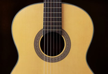 Close-up Wooden Spanish Classic Guitar With Nylon String On The Dark Background