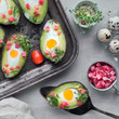 Keto diet dish: Avocado boats with ham cubes, quail eggs and cherry tomatoes