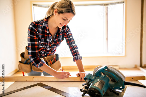 Obraz A woman worker in the carpenter workroom renovation - fototapety do salonu