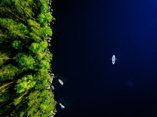 Aerial View Of Blue Lake With A Fishing Boat And Green Forests With Rocks In Finland.