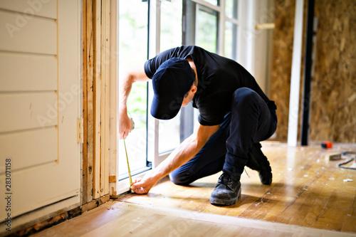 Cuadros en Lienzo  A handsome young man installing Double Sliding Patio Door in a new house constru