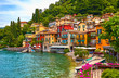Leinwandbild Motiv Varenna, Italy. Picturesque town at lake Como. Colourful motley Mediterranean houses on knoll by coastline among green trees. Popular health resort and touristic destination location. Summer day.